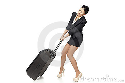 Business woman pulling her heavy suitcase