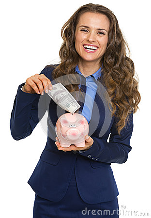 Business woman putting 100 dollars banknote into piggy bank