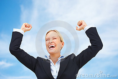 Business woman raising her arms in joy with sky