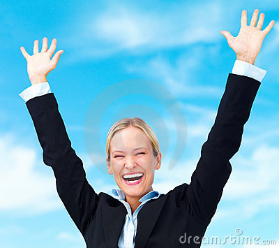Business woman raising her arms in joy to sky