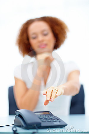 Business woman reaching for the phone