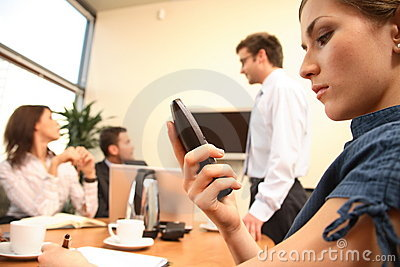 business woman reading message on mobile phone. presentation in background.