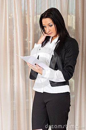 Business woman reading papers in office