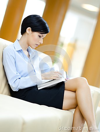Business woman relaxes at the sofa with book