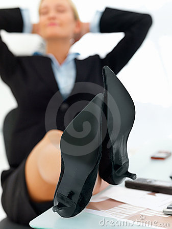 Business woman resting with legs on table