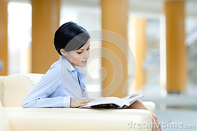 Business woman rests at the sofa with book