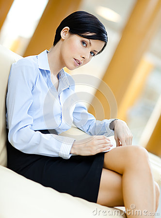 Business woman rests at the sofa handing book