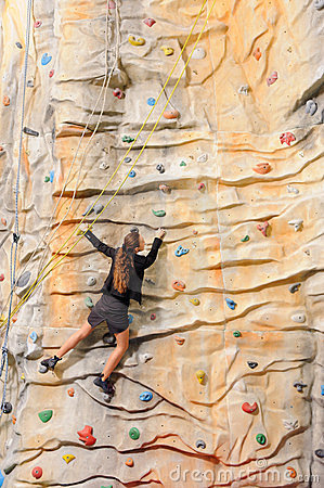 Business woman on rock wall