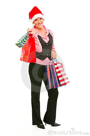 Business woman in Santa Hat holding shopping bags