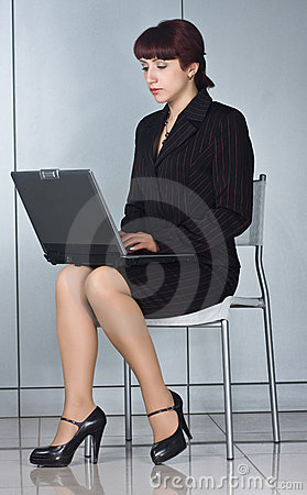 Business woman sitting on chair with laptop