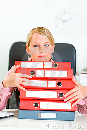 Business woman sitting at desk with folders