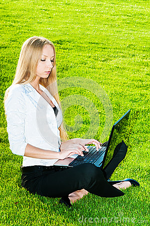 Business woman sitting on the grass