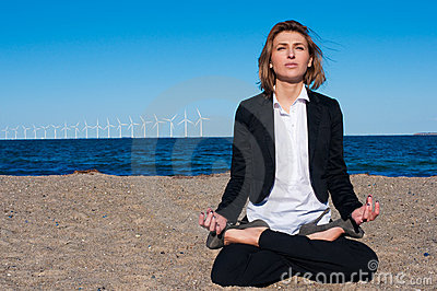 Business woman sitting in lotus pose on the beach,