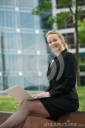 Business woman sitting outdoors and smiling with laptop