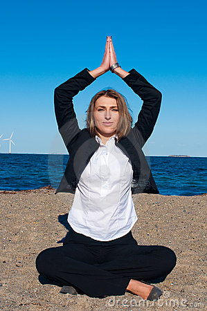 Business woman sitting in yoga pose on the beach
