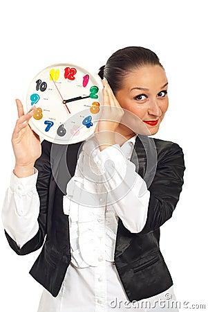 Business woman smiling behing clock