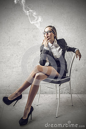 Young beautiful business woman smoking a cigarette sitting on a chair.