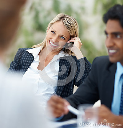 Business woman speaking on the phone at a meeting