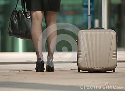 Business woman standing with bag and suitcase