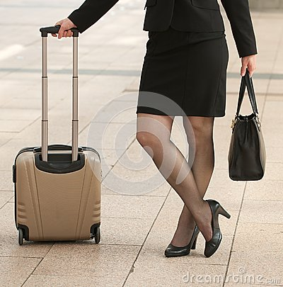 Business woman standing with bags on sidewalk
