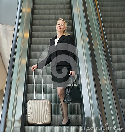 Business woman standing on escalator with travel bags