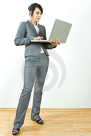 Business woman standing holding laptop