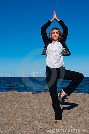 Business woman standing in yoga pose on the beach