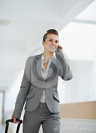 Business woman in trip with bag speaking mobile