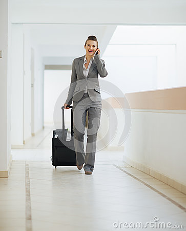 Business woman in trip walking with wheel bag
