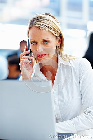 Business woman using a laptop and cellphone