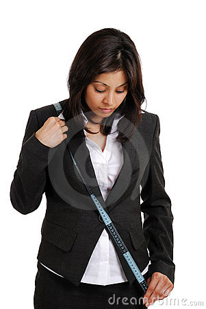 Business woman using a measuring tape looking down