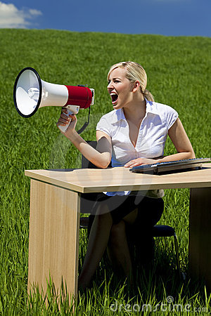 Business Woman Using Megaphone In A Green Field