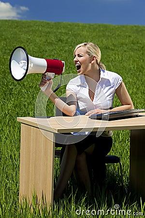 Business Woman Using Megaphone In A Green Field