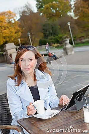 Business woman using tablet on lunch break.