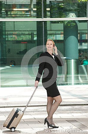 Business woman walking and calling with mobile phone outdoors