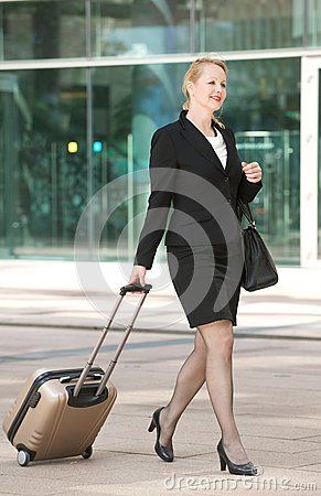 Business woman walking int he city with travel bag and luggage