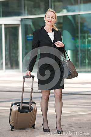 Business woman walking outdoors with luggage