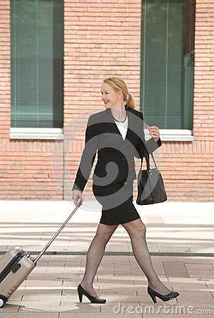 Business woman walking with travel luggage in the city