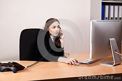 Business woman working on her computer and calling