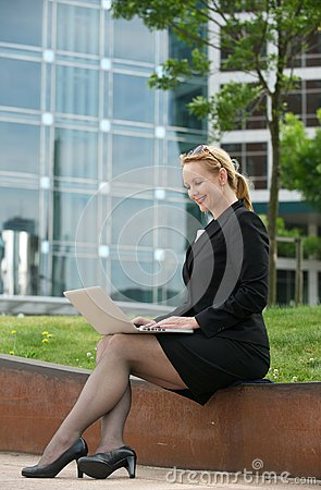 Business woman working on laptop outside the office