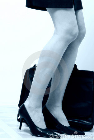 Business womans legs beside briefcase