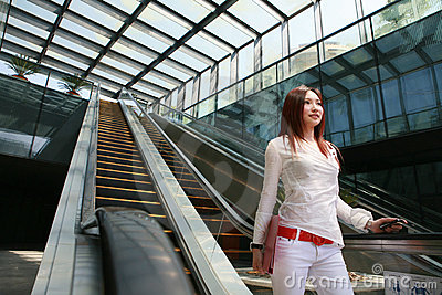 Business women holding mobile phone on escalator