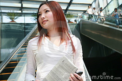 Business women holding mobile phone and newspaper