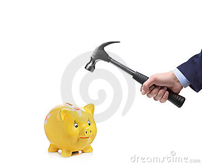 Businessman's hand about to break a piggy bank