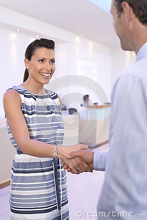 Free Businessman And Woman Shaking Hands In Foyer, Smiling, Close-up Stock Photo - 41710040