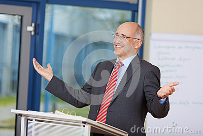 Businessman With Arms Raised Standing At Podium
