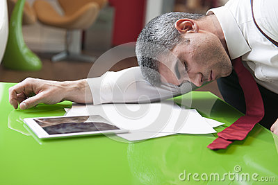 Businessman asleep on documents