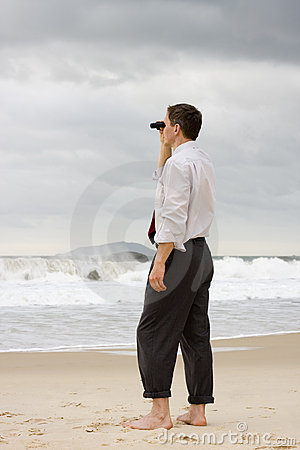 Businessman on a beach searching with binoculars
