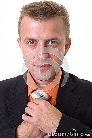Businessman with beard adjusting his tie