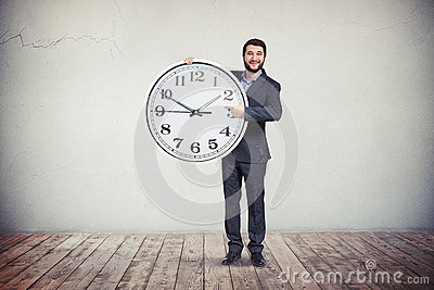 Businessman with big round clock in his hands